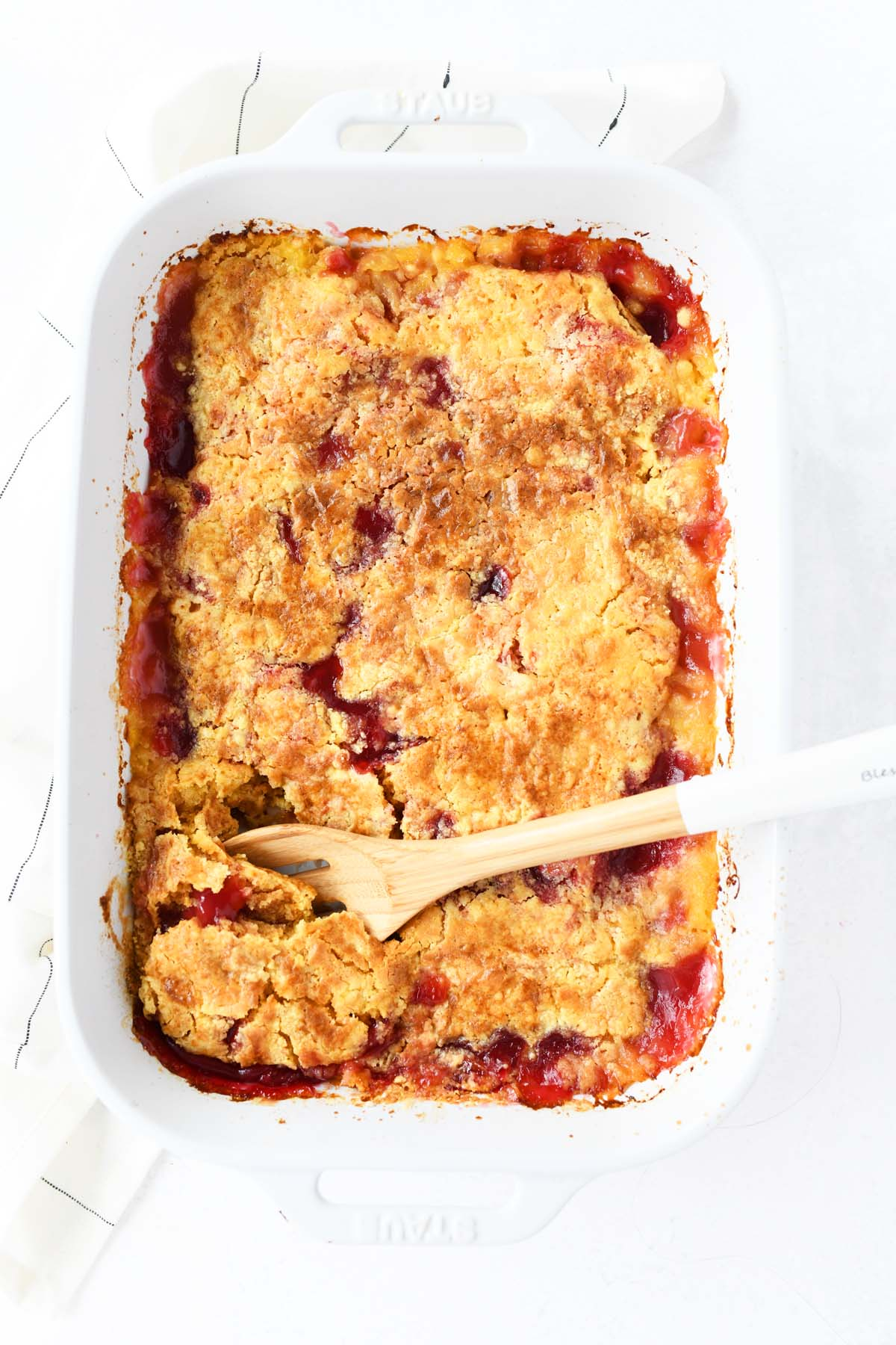 Cherry pineapple dump cake with a wooden spoon.