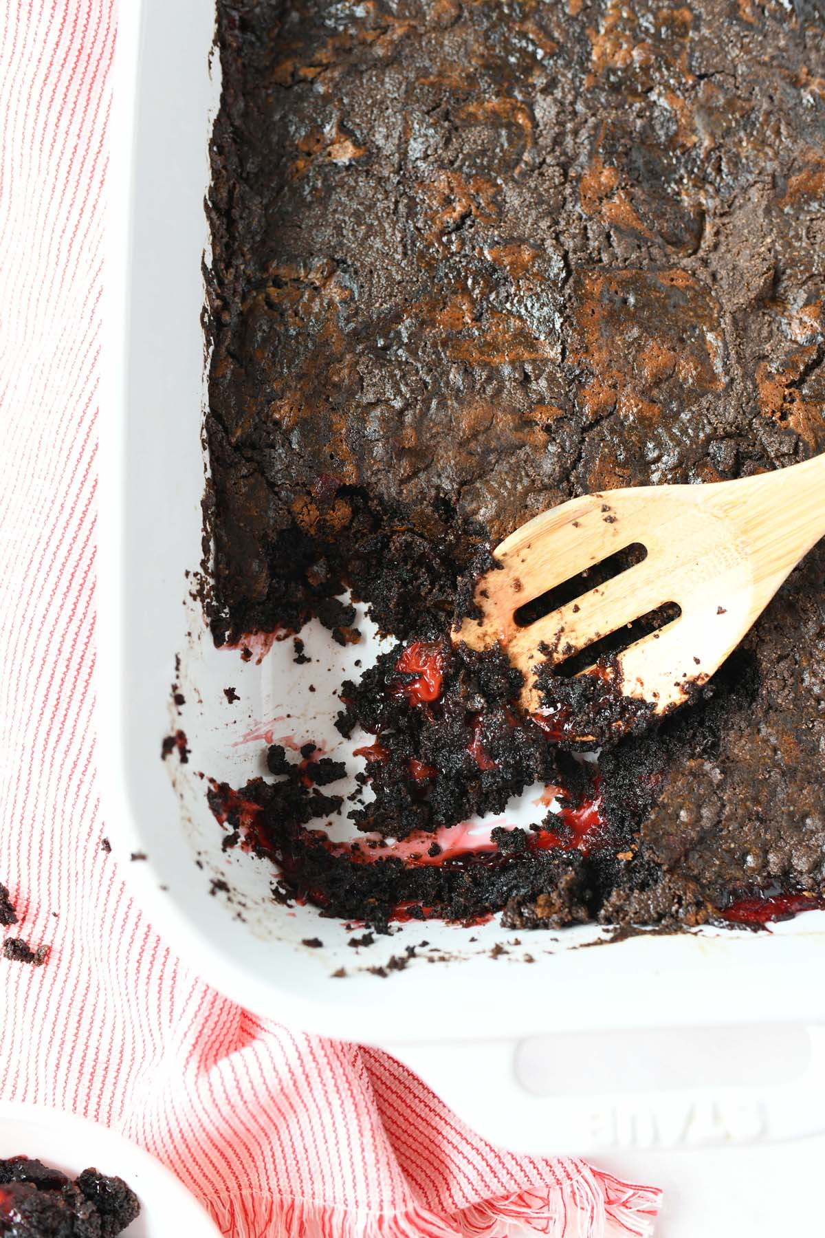Chocolate Cherry Dump Cake with a wooden spoon.