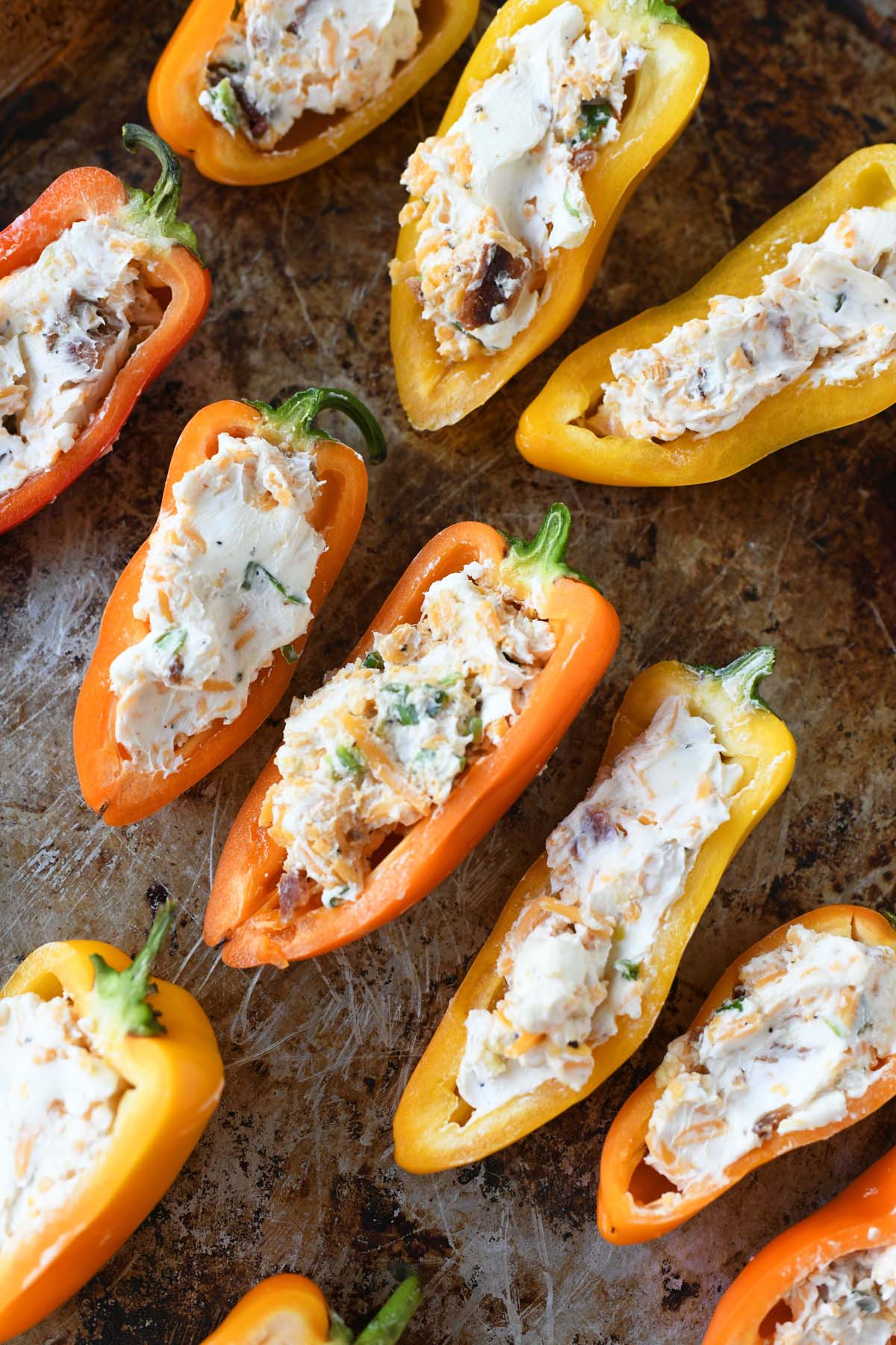 Rainbow peppers stuffed with cheese and bacon on a baking sheet.
