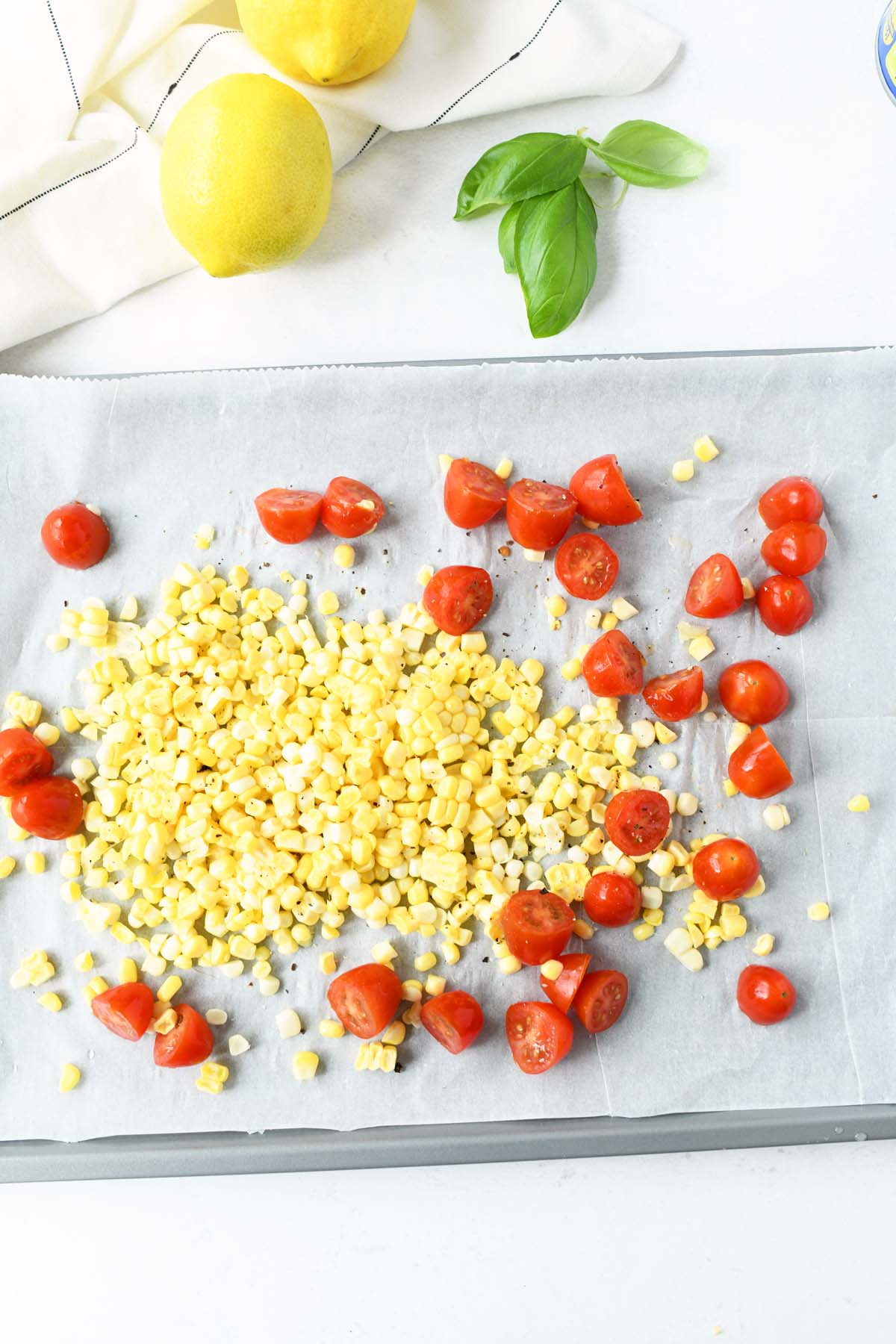 Roasted corn and tomato on a baking sheet.