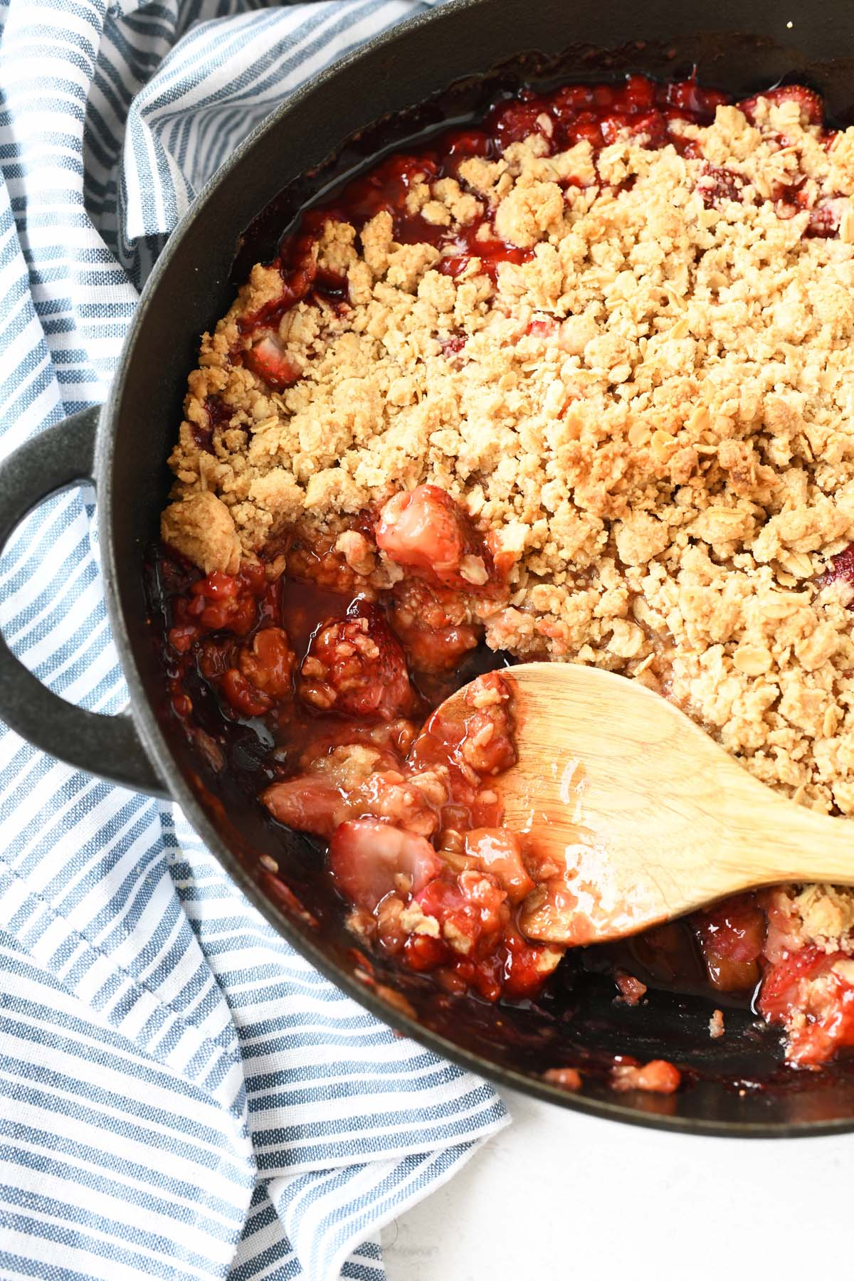 berry rhubarb crisp in cast iron pan with a wooden spoon.