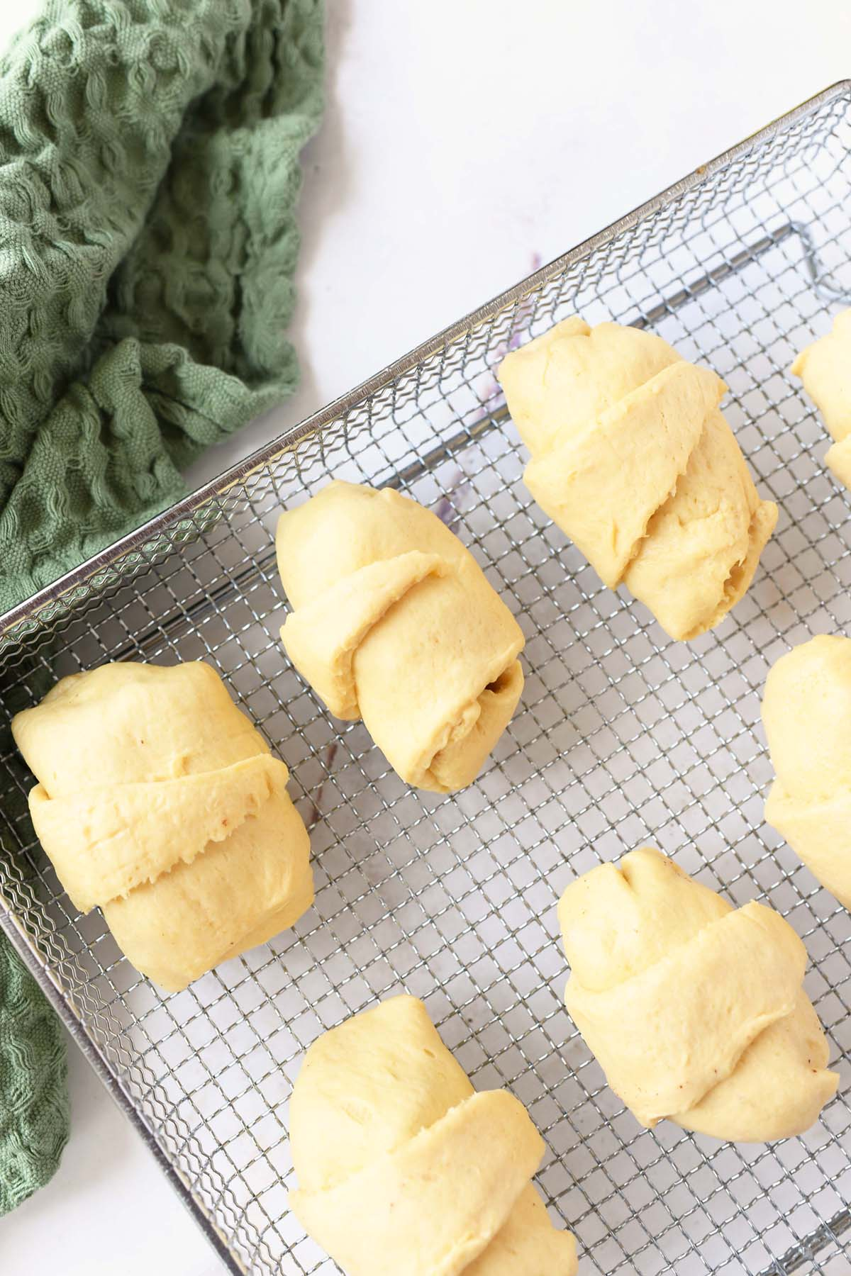 raw crescents on an air fryer pan.