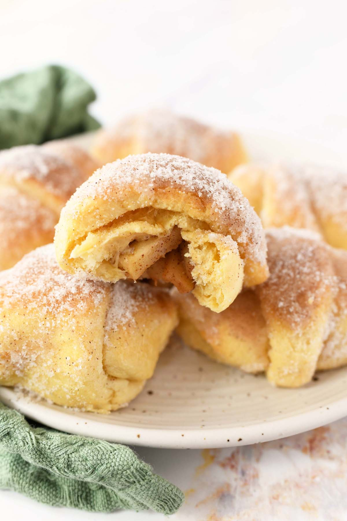Apple Pie Crescent Rolls stacked on a white plate.