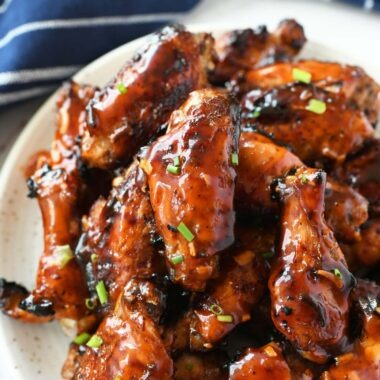 Apricot sticky chicken wings on a white plate with a blue napkin.