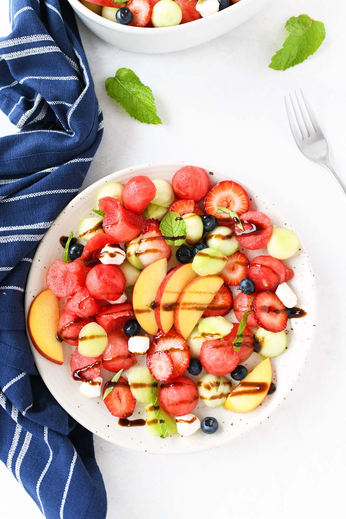 Caprese Melon Salad with glaze in a white plate.