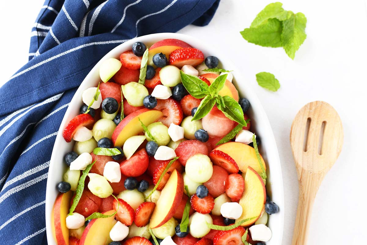 Colorful Fruit Salad Caprese near a wooden spoon and blue napkin.