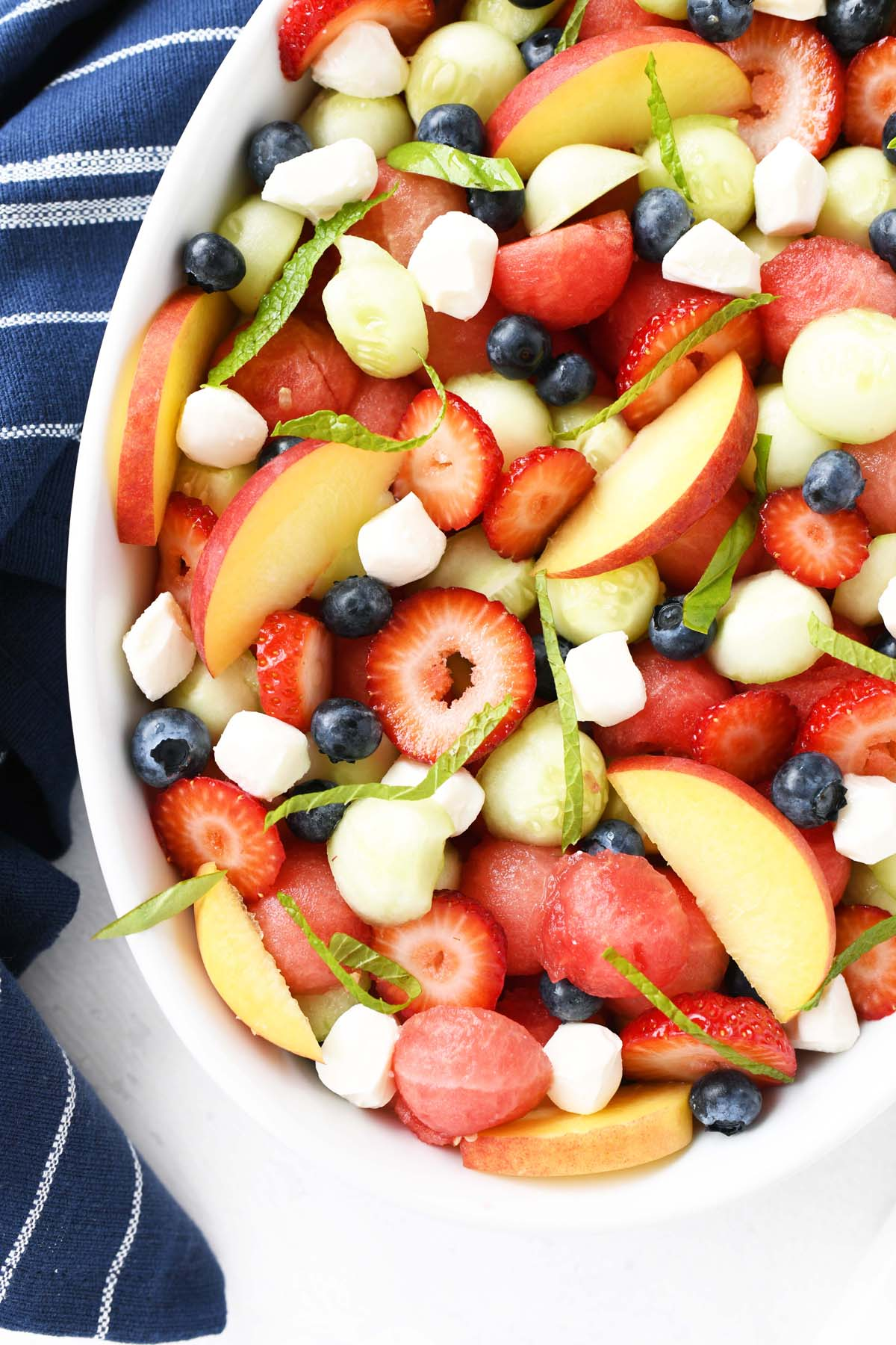 Melon Berry Caprese Salad in an oval white bowl with a blue napkin.