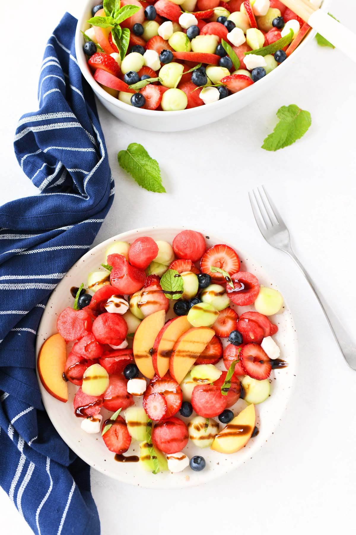 Melon Caprese Salad with a fork in a white plate.