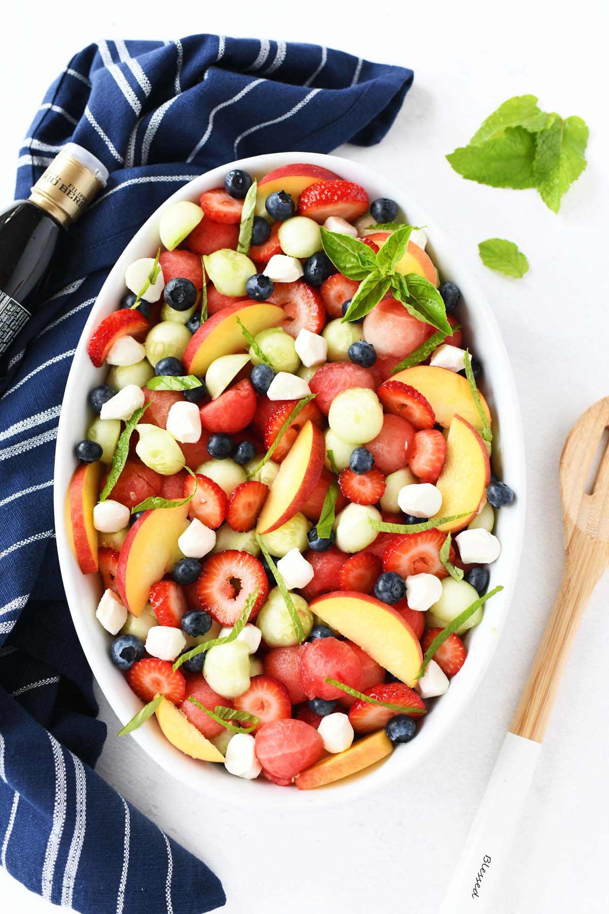 A white oval baker with colorful fruits and green leaves.