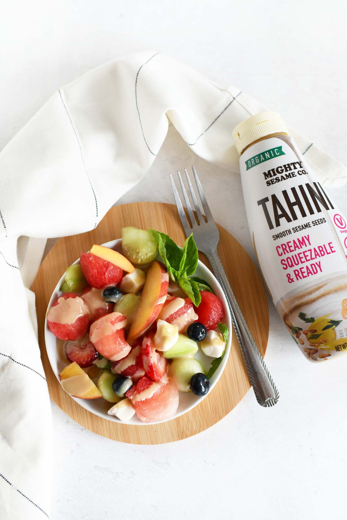 Tahini Fruit Salad in a small white plate with a fork.