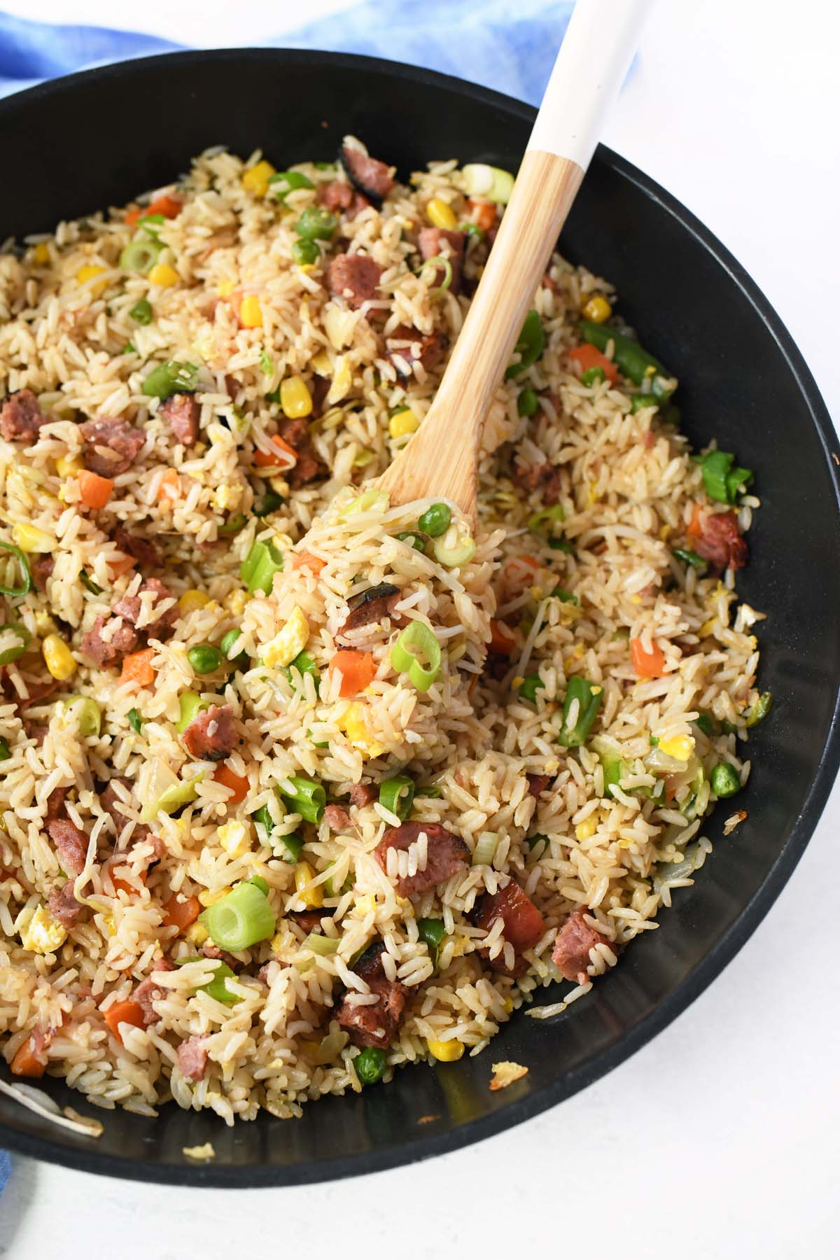Chinese Fried Rice in a black wok with a wooden spoon.