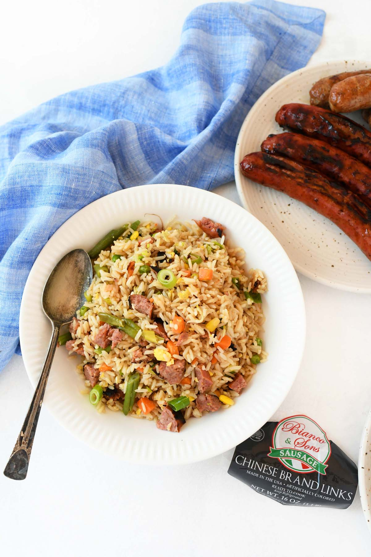 Chinese Sausage Fried Rice in white bowl with a rustic spoon.