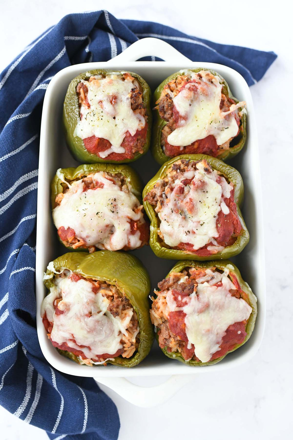 Baked Green bell peppers with cheese in a white baker.
