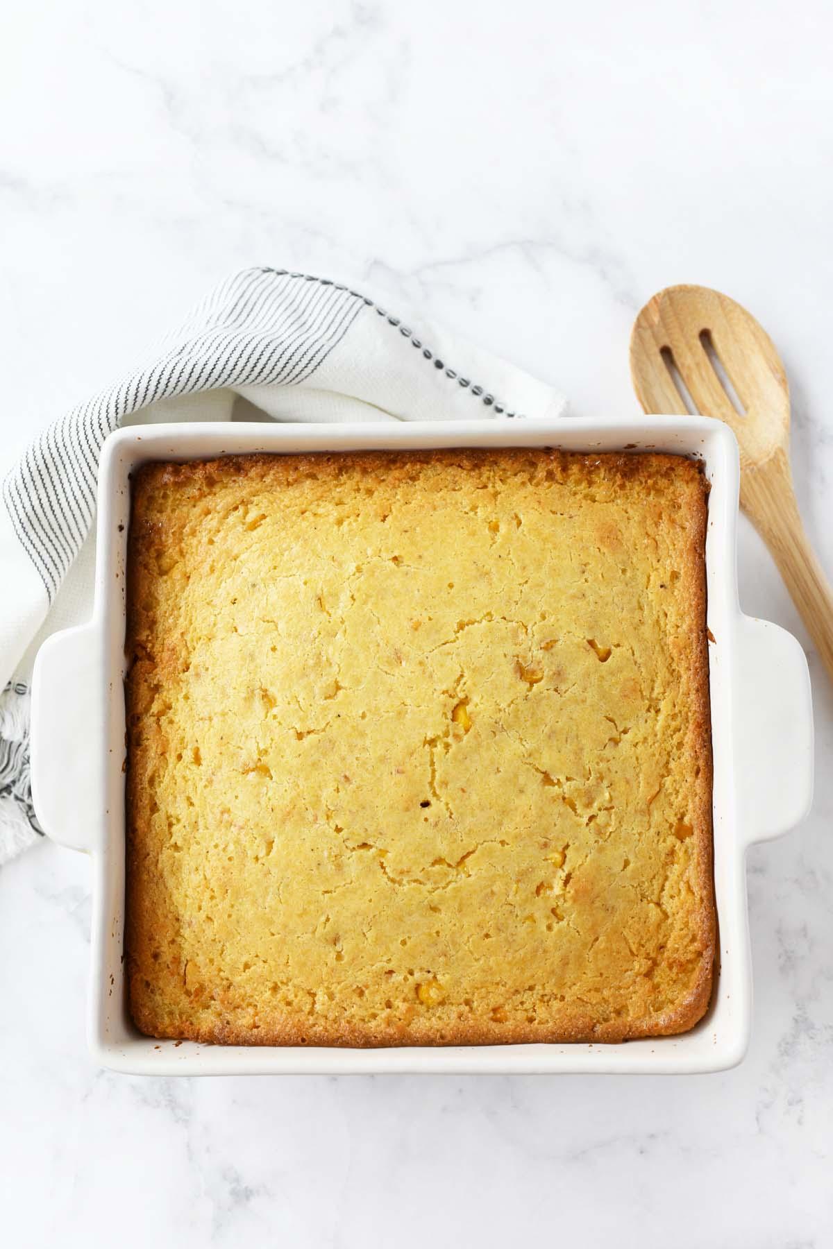 Jiffy corn casserole in a white baker.