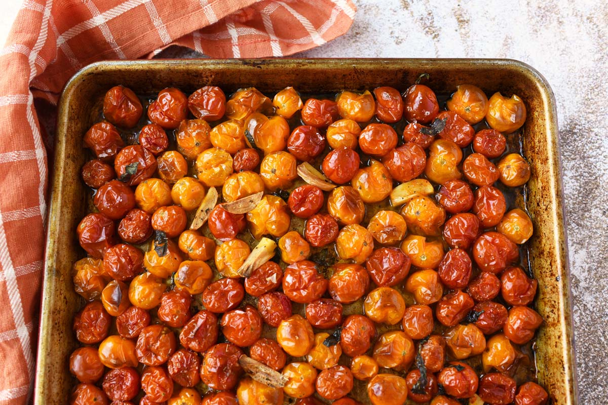 Oven Roasted cherry tomatoes on a rustic baking sheet.