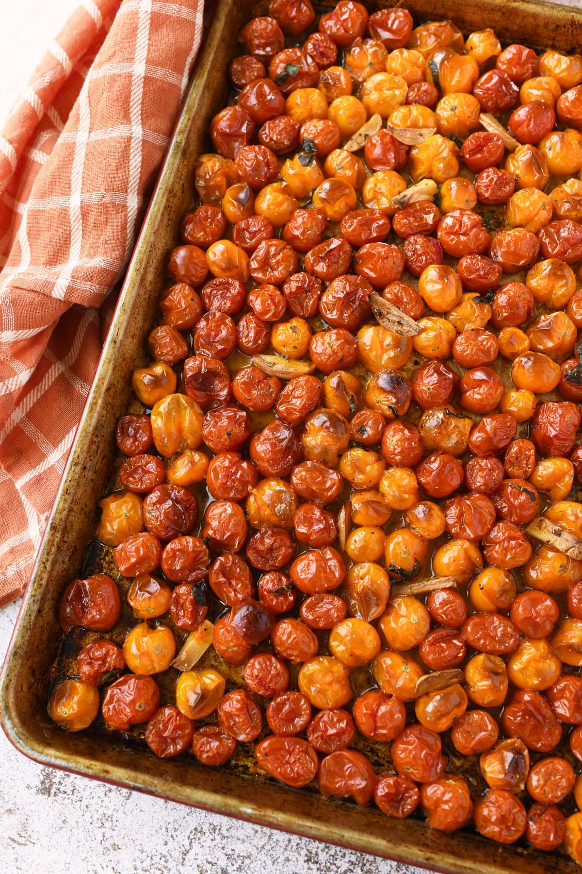 Oven roasted cherry tomatoes with garlic on a worn baking sheet.
