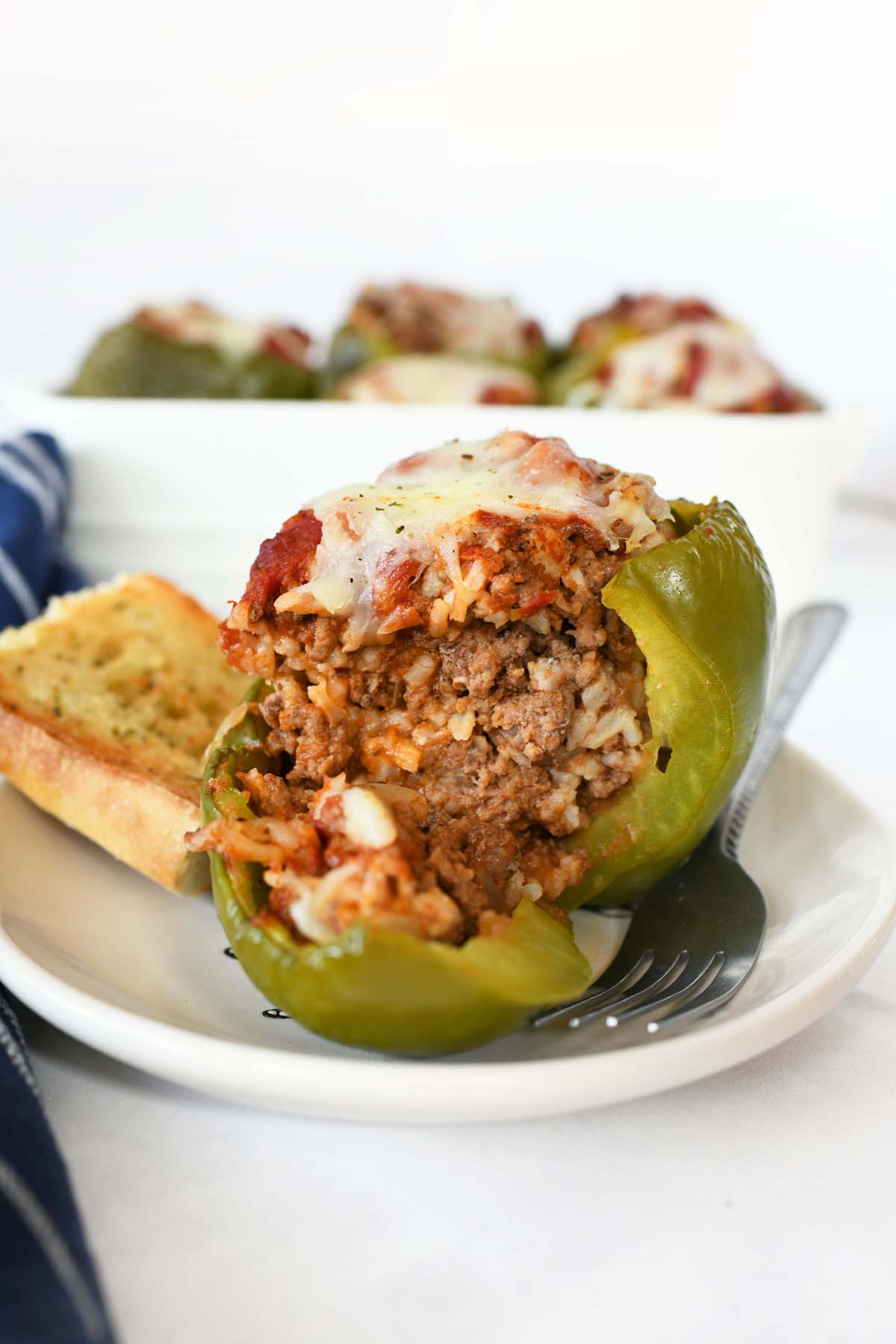 Stuffed Green Bell Peppers with meat and rice cut open to show the insides.