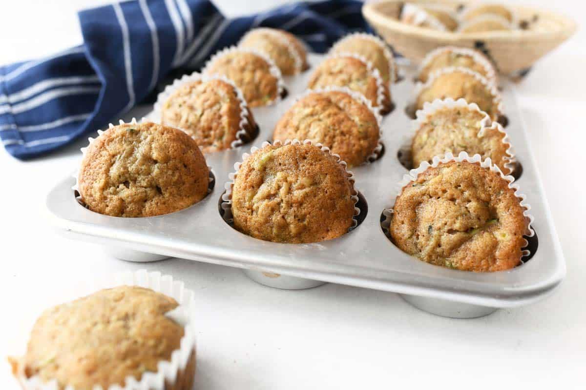 Super moist zucchini muffins in a metal muffin tin.