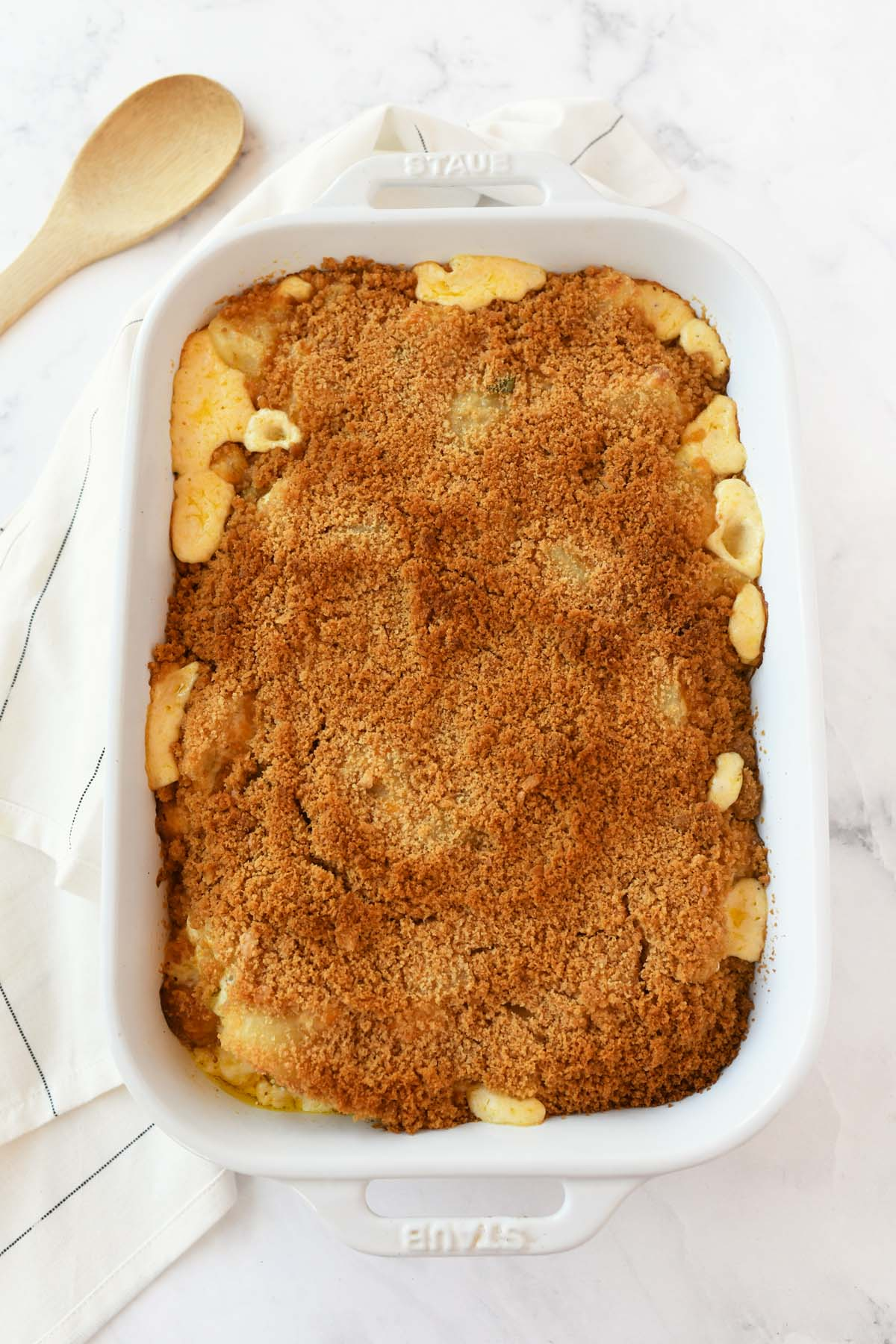 Golden browned funeral potatoes in a white baker.
