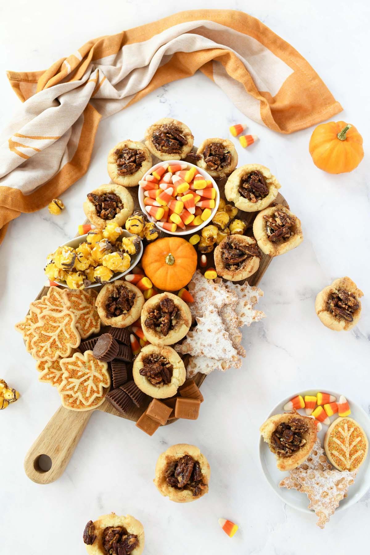 Harvest Snack Board with orange napkins and pumpkins.
