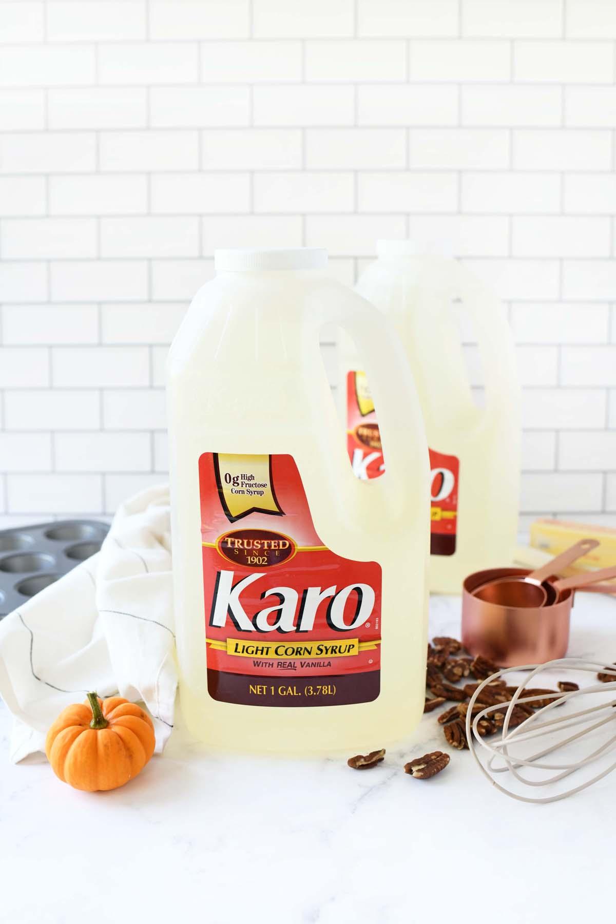 Karo Corn Syrup jugs on a white table near a mini pumpkin.