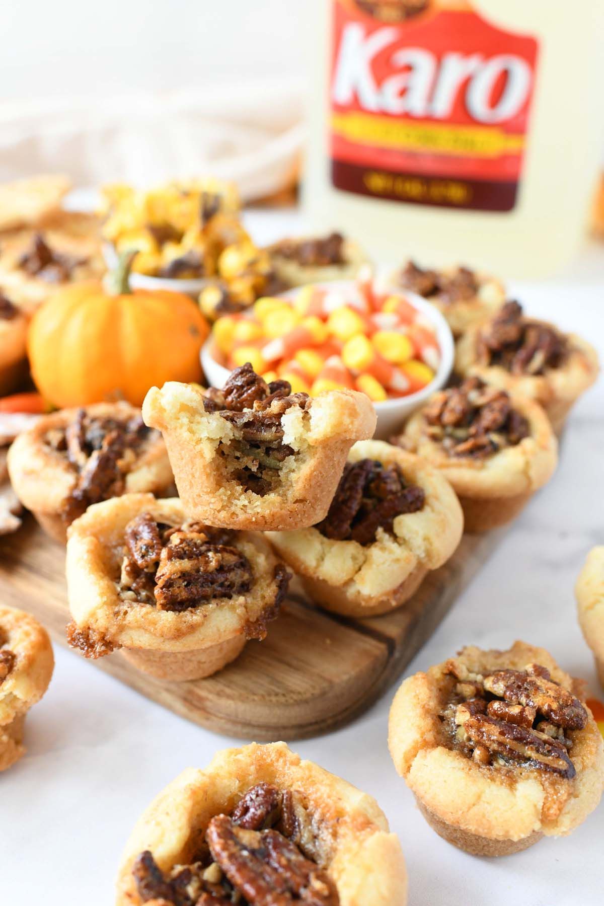 Pecan Sugar Cookie Cups on a wooden board with mini pumpkins and candy corn.