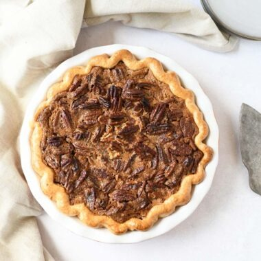 A baked pumpkin pecan pie on a white table.