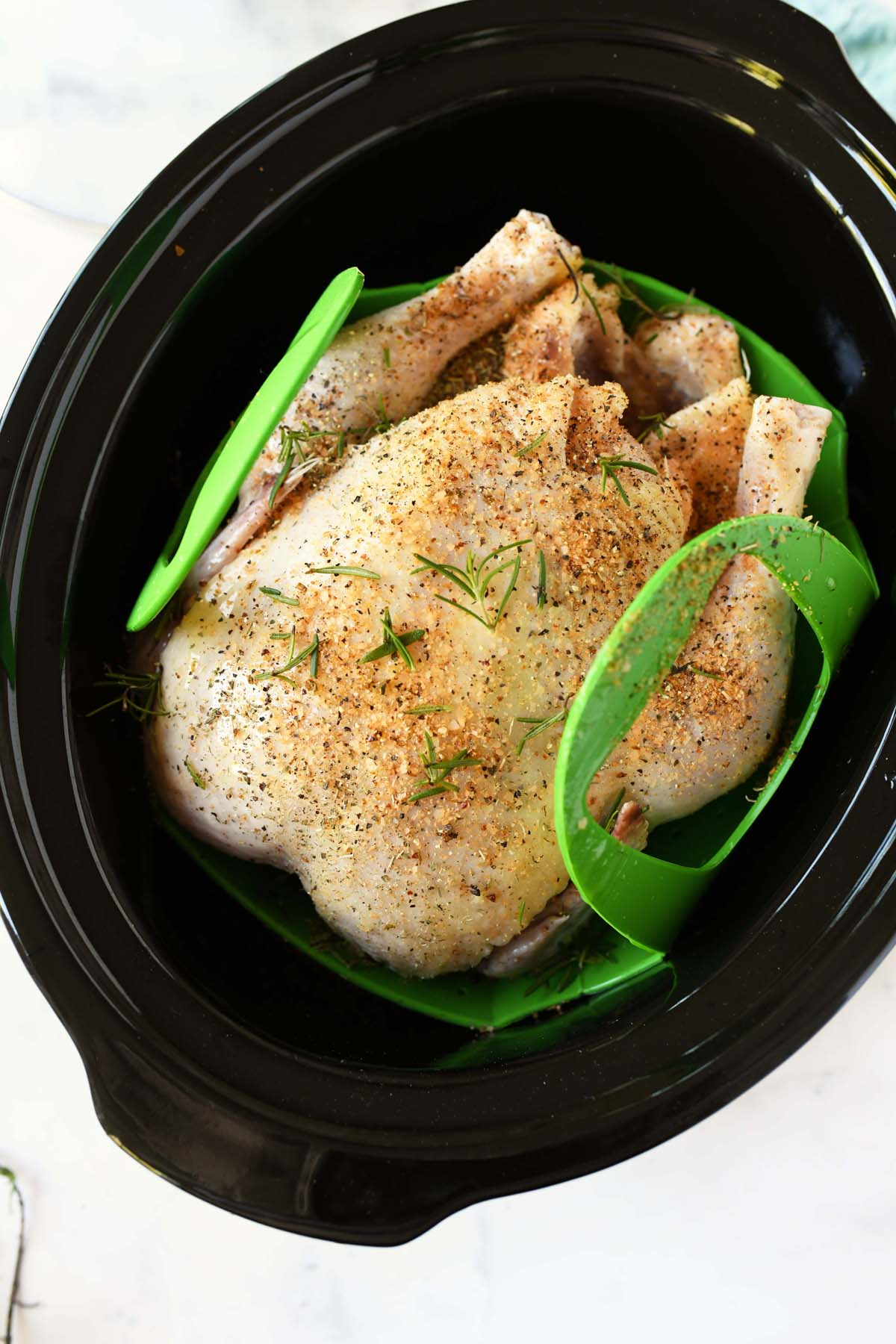 Whole seasoned chicken on a green sling in the slow cooker.