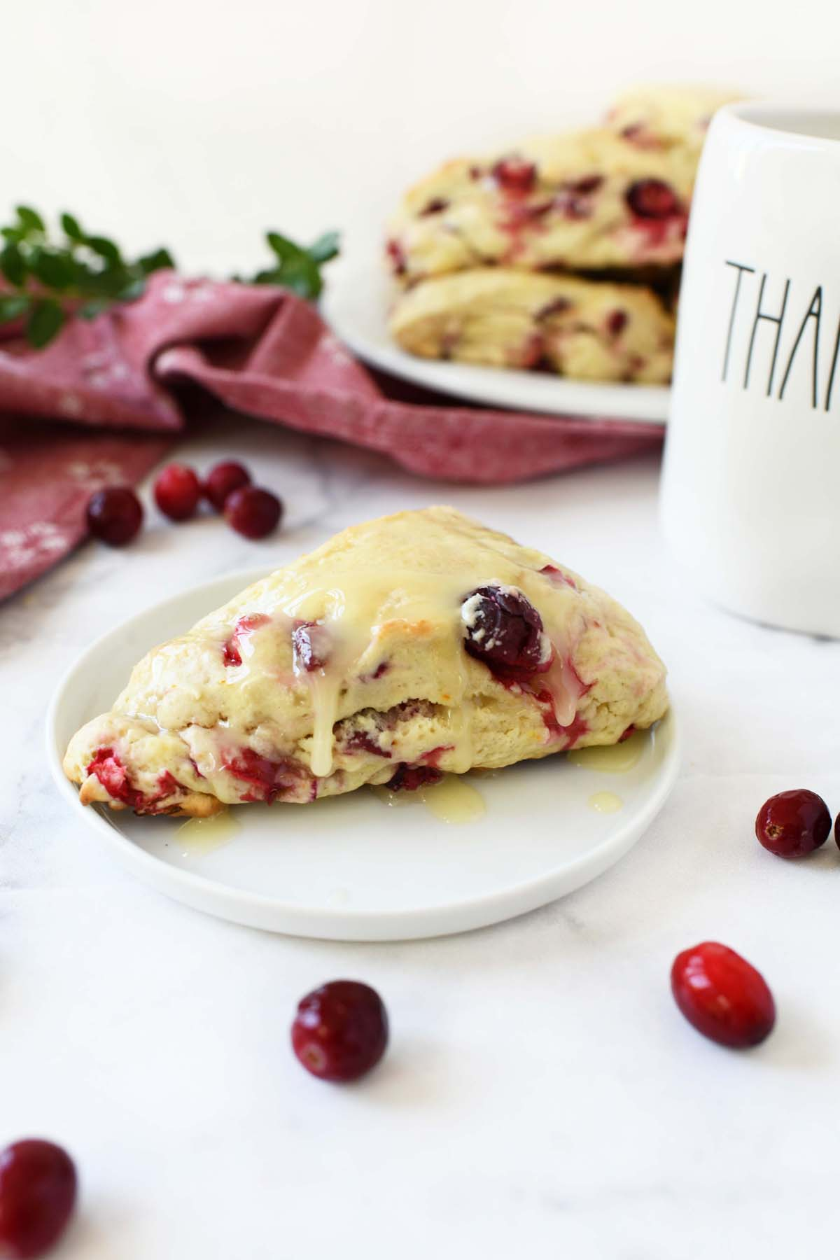 Cranberry Orange Scone on a plate with a thankful cup.