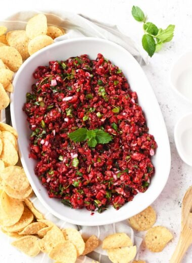 Cranberry salsa in a white dish with chips.