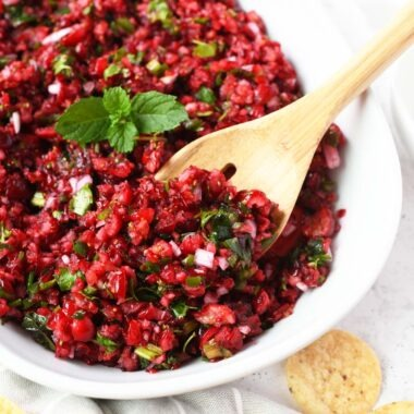 Cranberry salsa with a wooden spoon inside it.