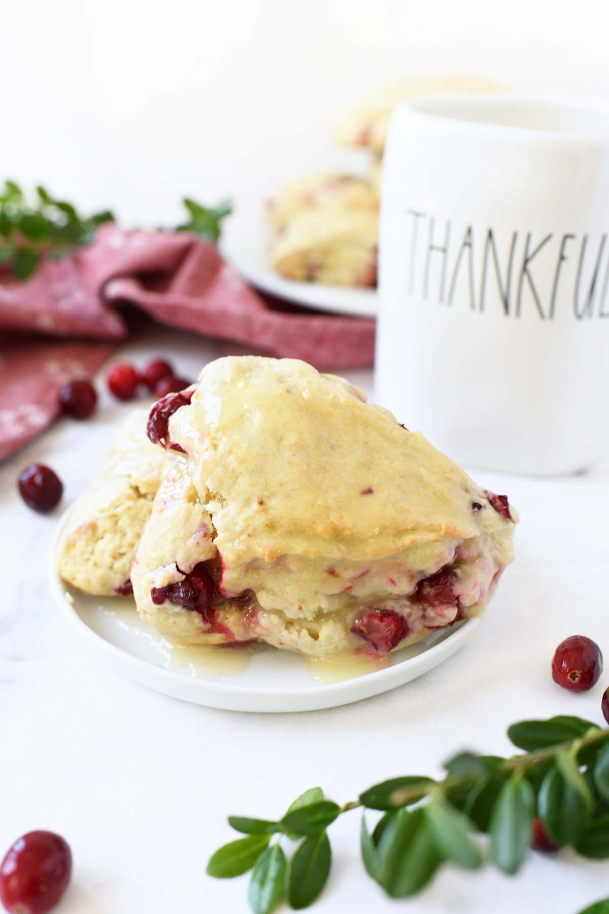 Glazed Cranberry Orange Scones on a plate with a thankful cup.