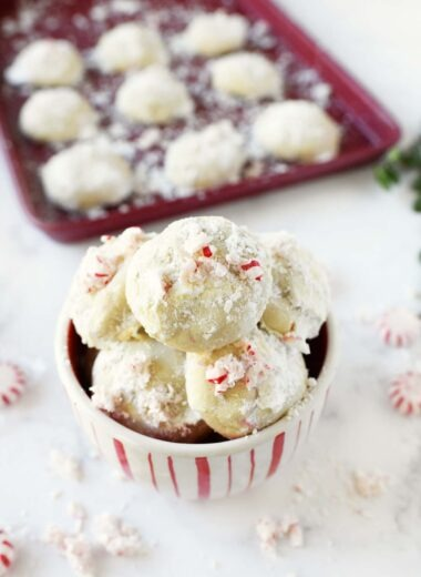 Snowball peppermint cookies are stacked in a red and white bowl.